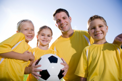 Coach with young players and soccer ball, 5 and 6 year olds
