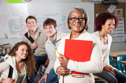 African American woman (50s) with class of high school or university students. Focus on teacher.
